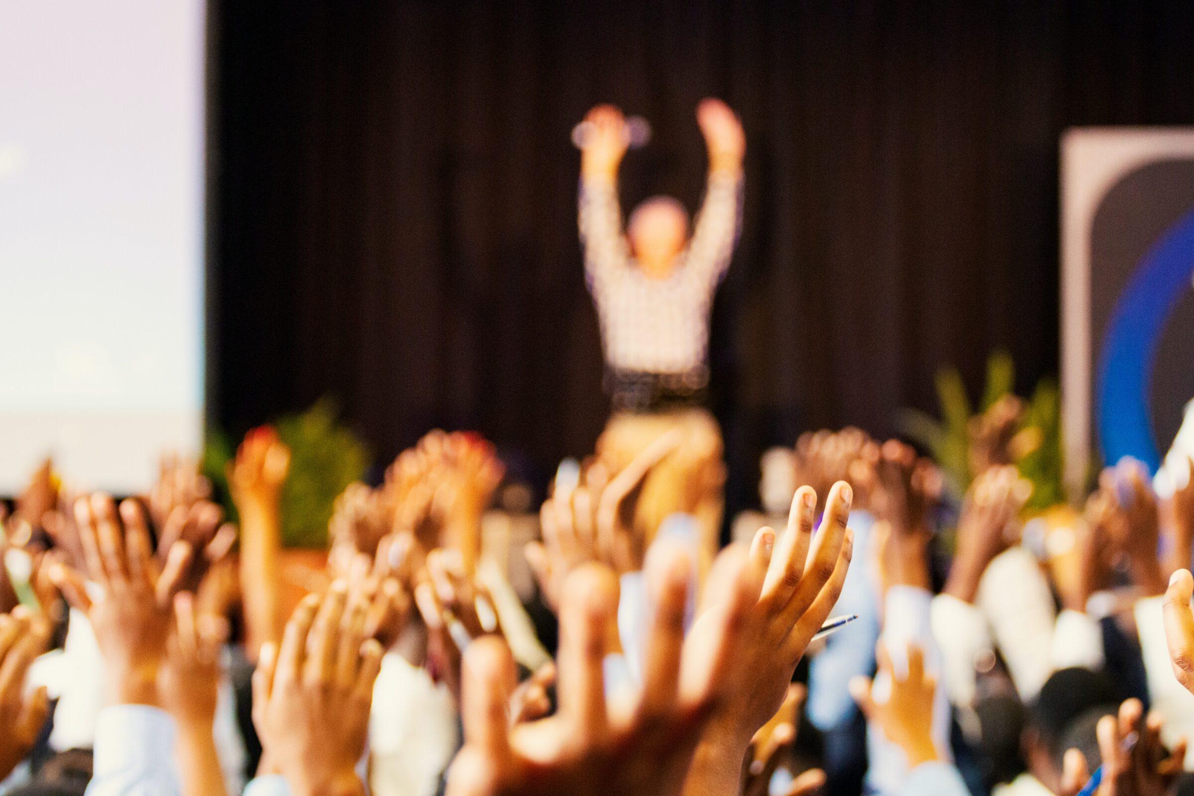 Opgestoken handen in de lucht met vaag op de achtergrond een man op het podium