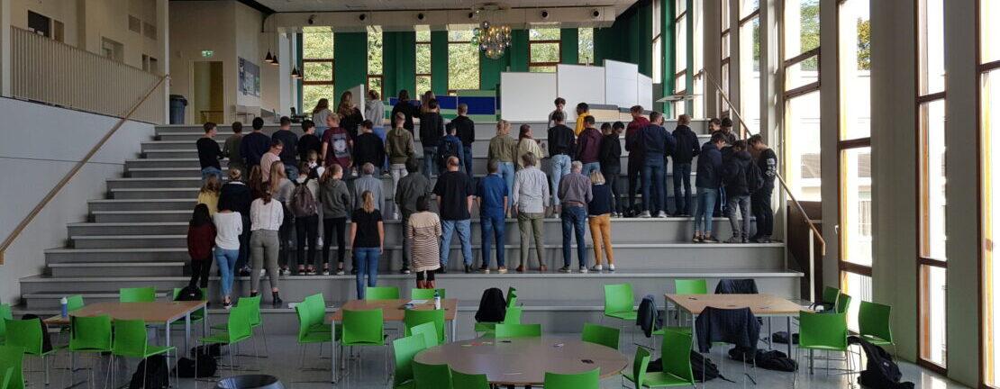 Jongeren in de aula met de ruggen afgebeeld, terwijl ze staan op een hele brede trap. Op de voorgrond tafels en stoelen waar ze les hebben gehad