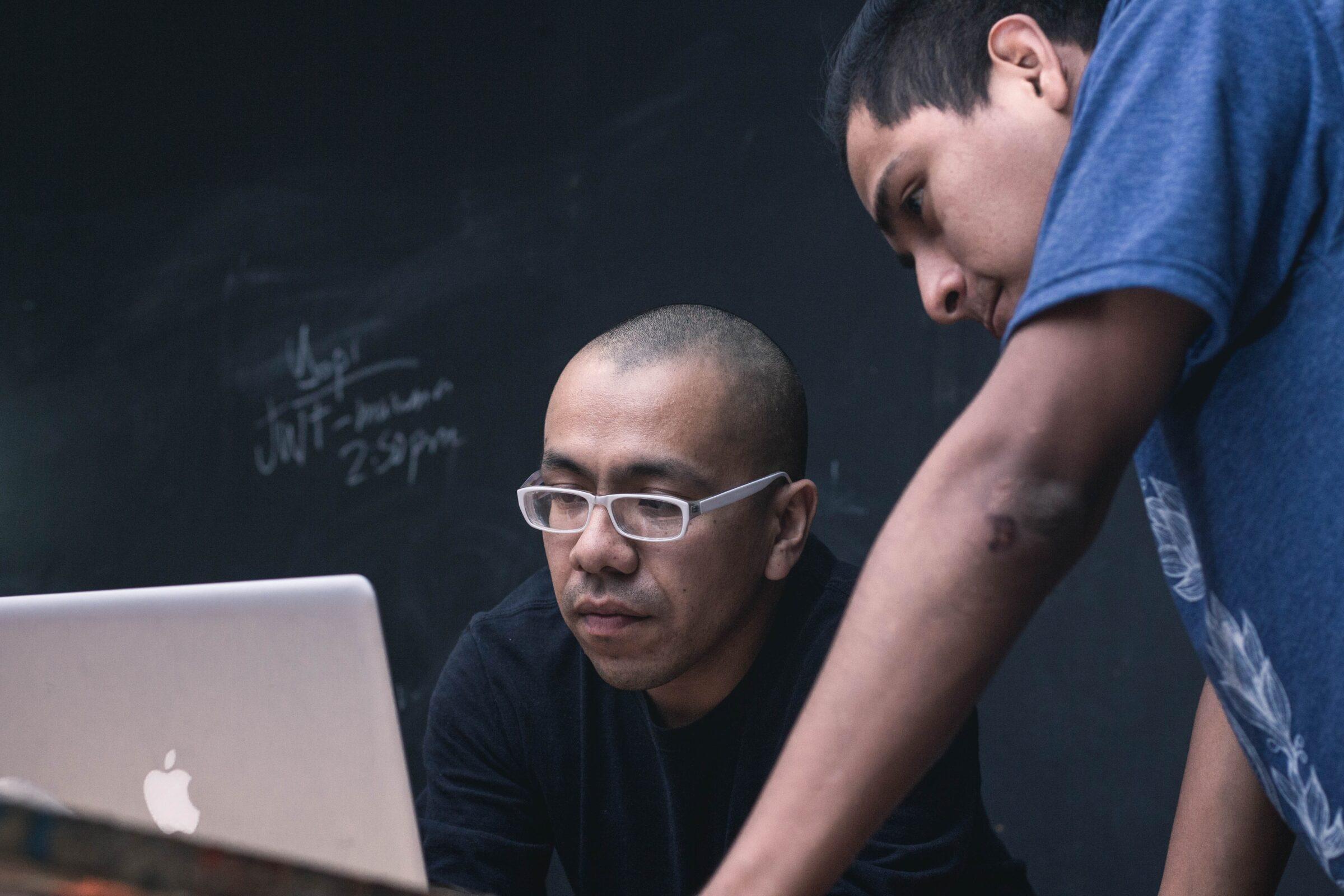 Man met bril zit voor computer, voor een schoolbord. Een andere man kijkt met hem mee